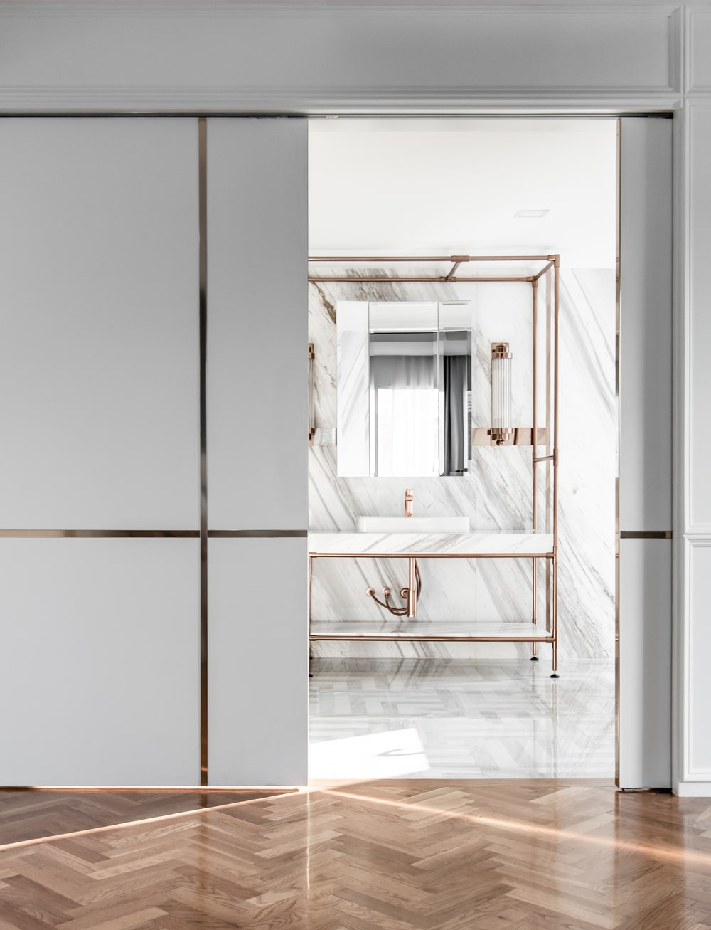A few steps from the bed is this sliding door that leads to the bathroom with golden accents on it.
