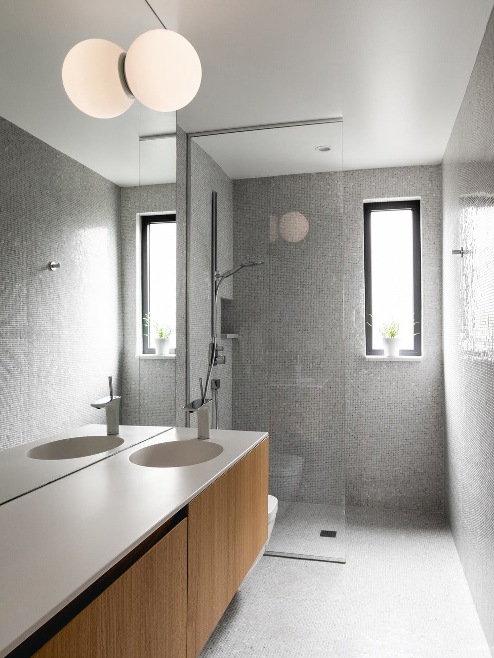 The glass-enclosed shower area has a thin window that brings in natural lighting.