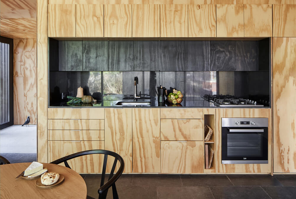This is a close look at the kitchenette with modern cabinetry contrasted by the dark countertop, backsplash and appliances.