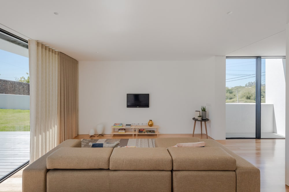 Across from the beige sofa is the wall-mounted TV and the wooden shelves underneath.