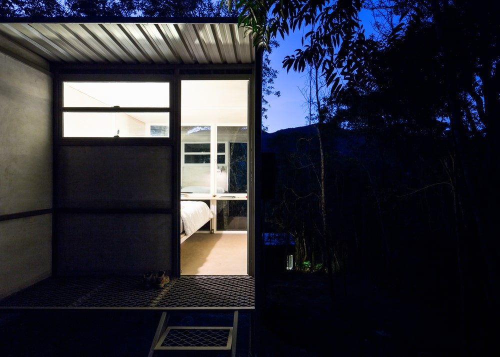 This is an exterior look at the bedroom door entrance with glass windows on the top to let the light escape.