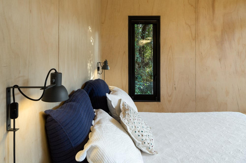 The wooden tone of the walls make the black wall-mounted lamps and window frame stand out.