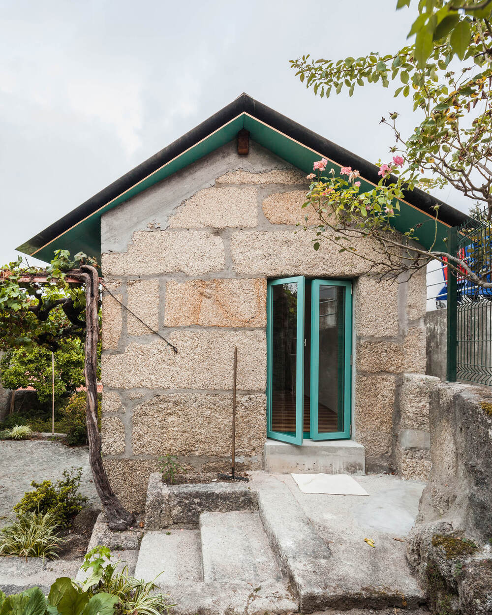 The exterior of the house has large adobe exterior walls adorned with small accents of green on the roof and window.
