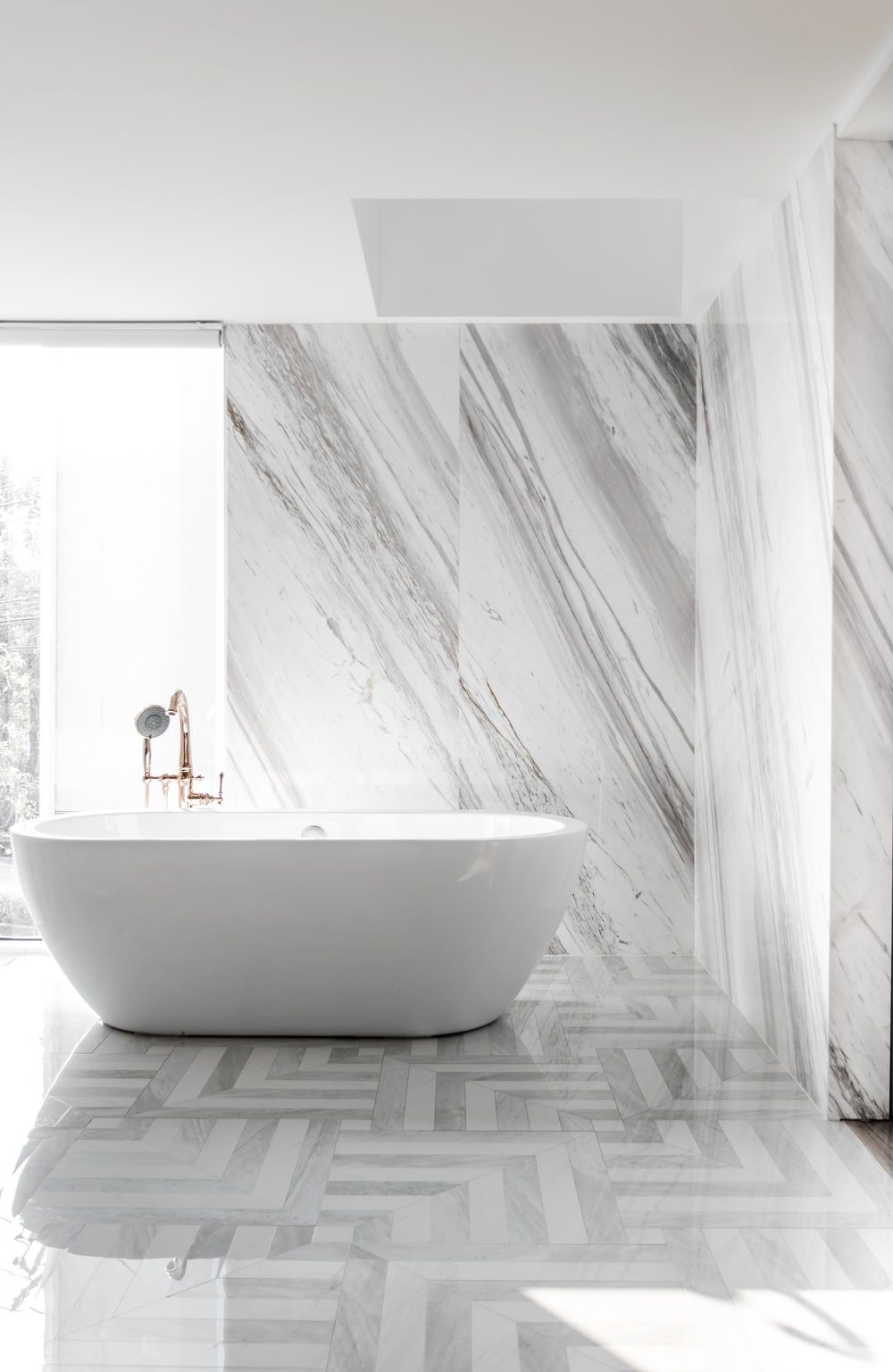 This is another look at the white porcelain freestanding bathtub that stands out against the white marble wall and patterned flooring tiles.