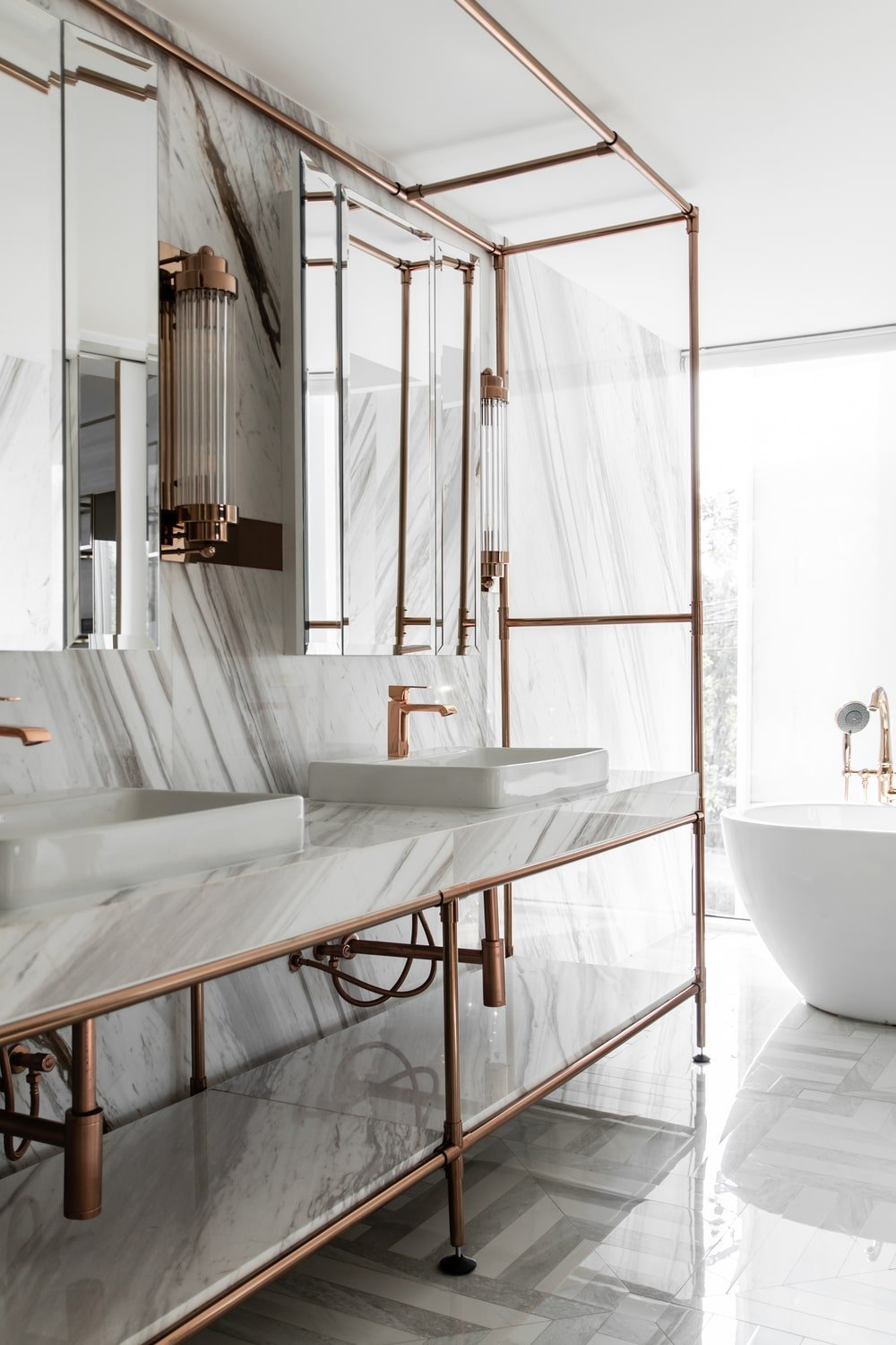 The white marble elements of this area is then complemented by the golden metallic frames and faucets.