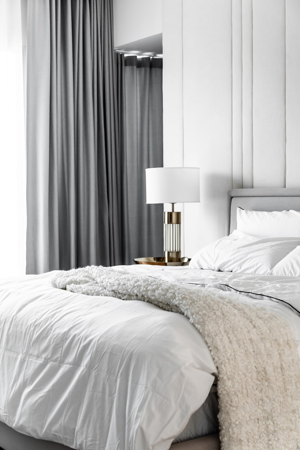 On the other side of the bed, the bedside table supports a table lamp that stands out against the gray curtains.