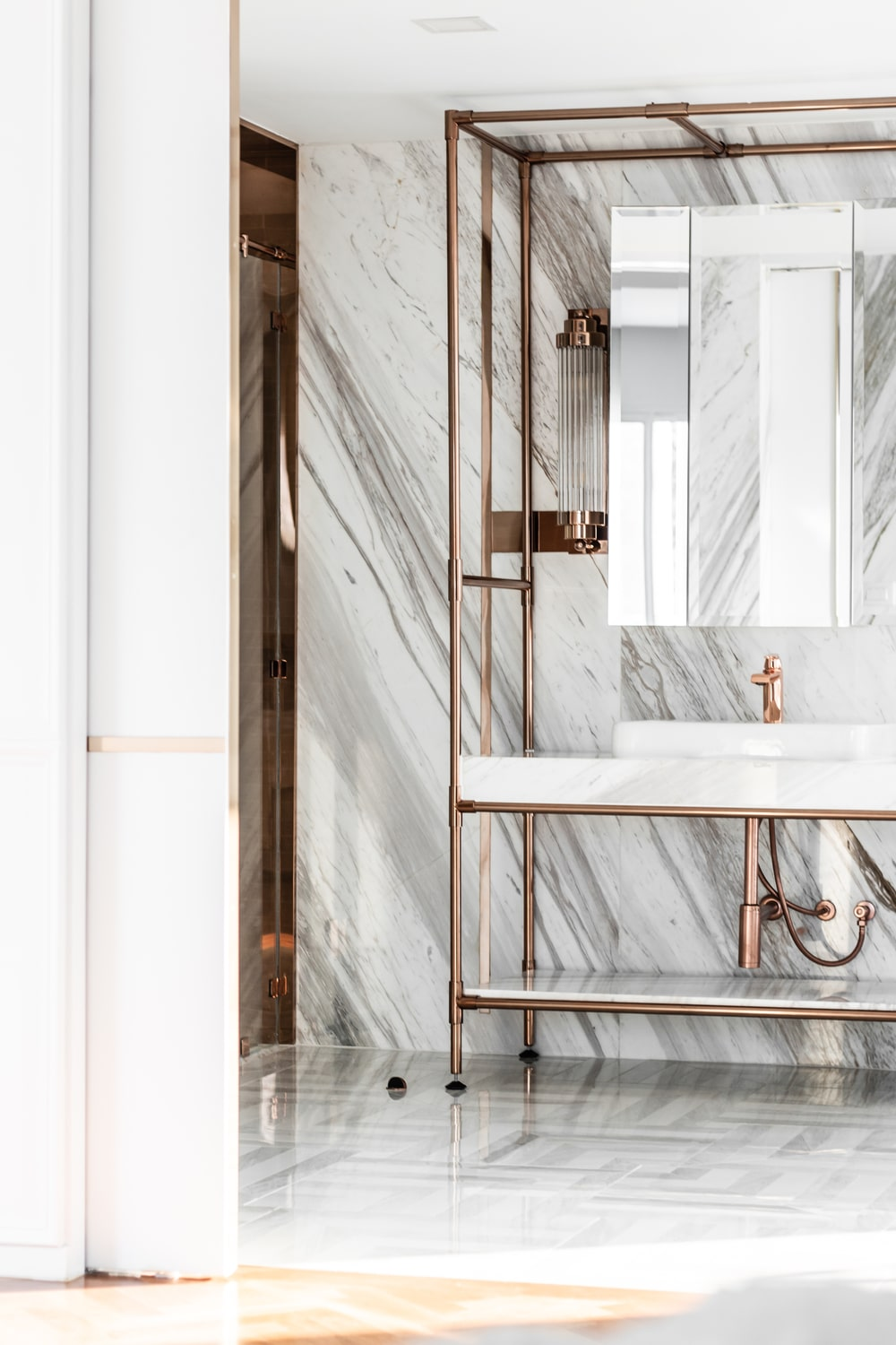 The two sinks of the vanity area is topped with wall-mounted mirrors that shine along with the white marble wall behind.