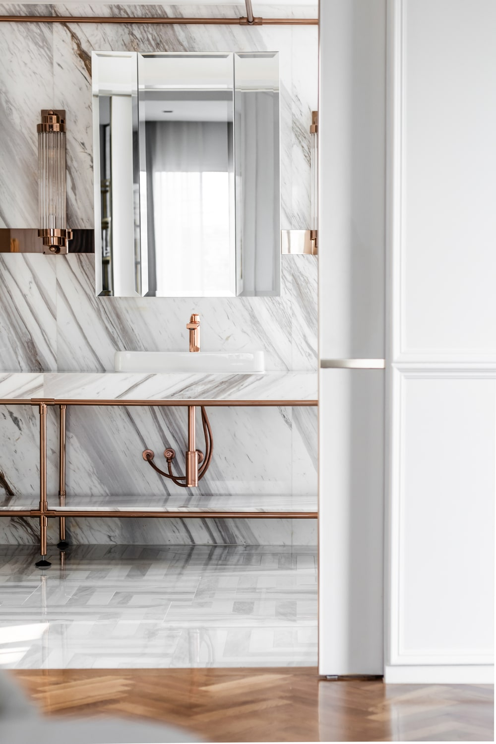 The white marble wall behind the vanity area also matches with the countertop of the two-sink vanity.