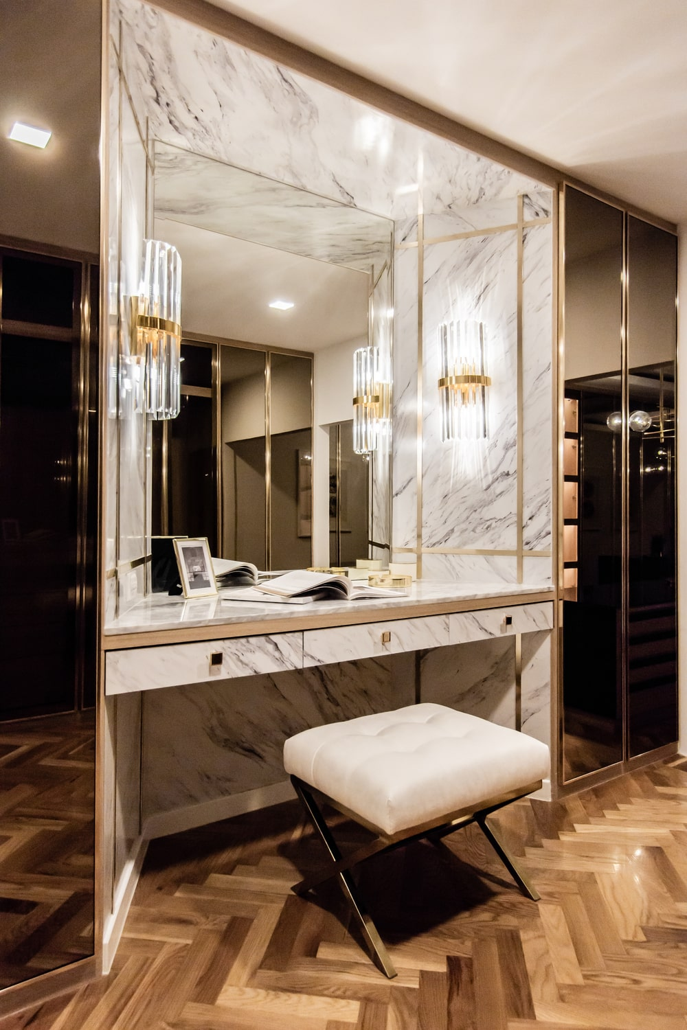 This is a close look at the luxurious vanity area within the walk-in closet of the house with a large mirror lit by sconces.