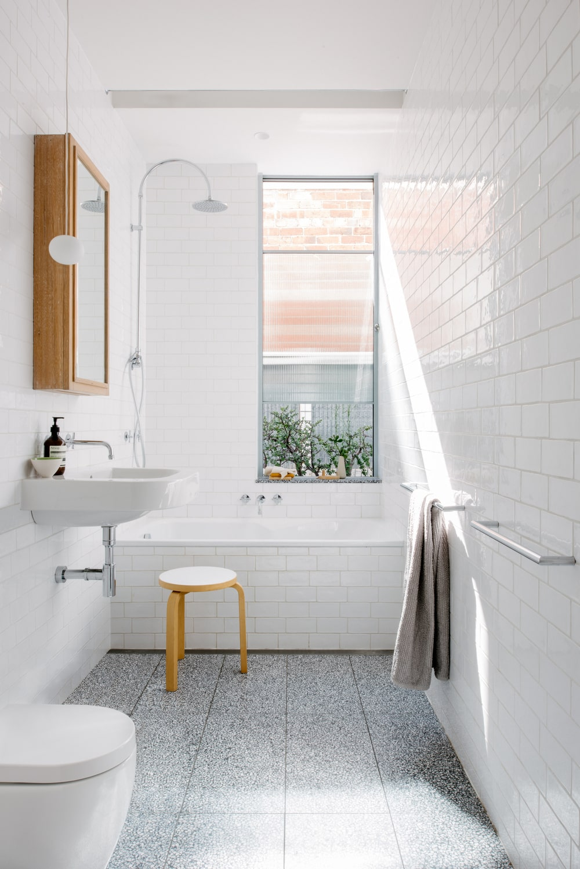 The bright white bathroom has a white bathtub at the far end by the window.