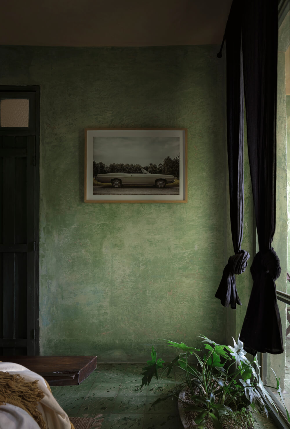 Across from the bed of the bedroom is a dark door with a wall-mounted artwork on the side by the window that has black curtains.