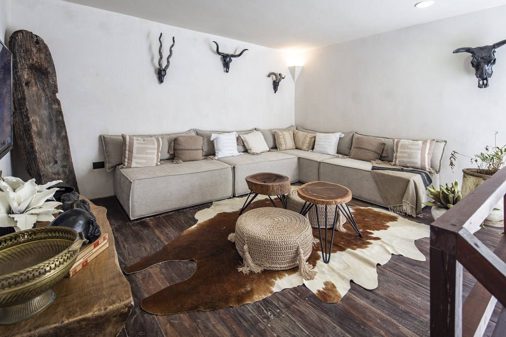 The living room has a large L-shaped sectional sofa adorned with wall-mounted animal skulls.