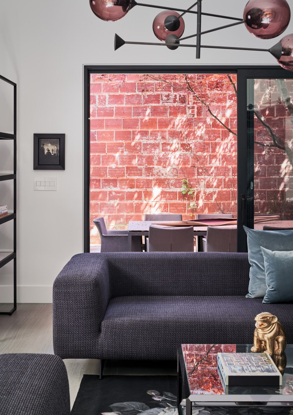 A few steps from the family room is the outdoor dining area by the large red brick wall outside.