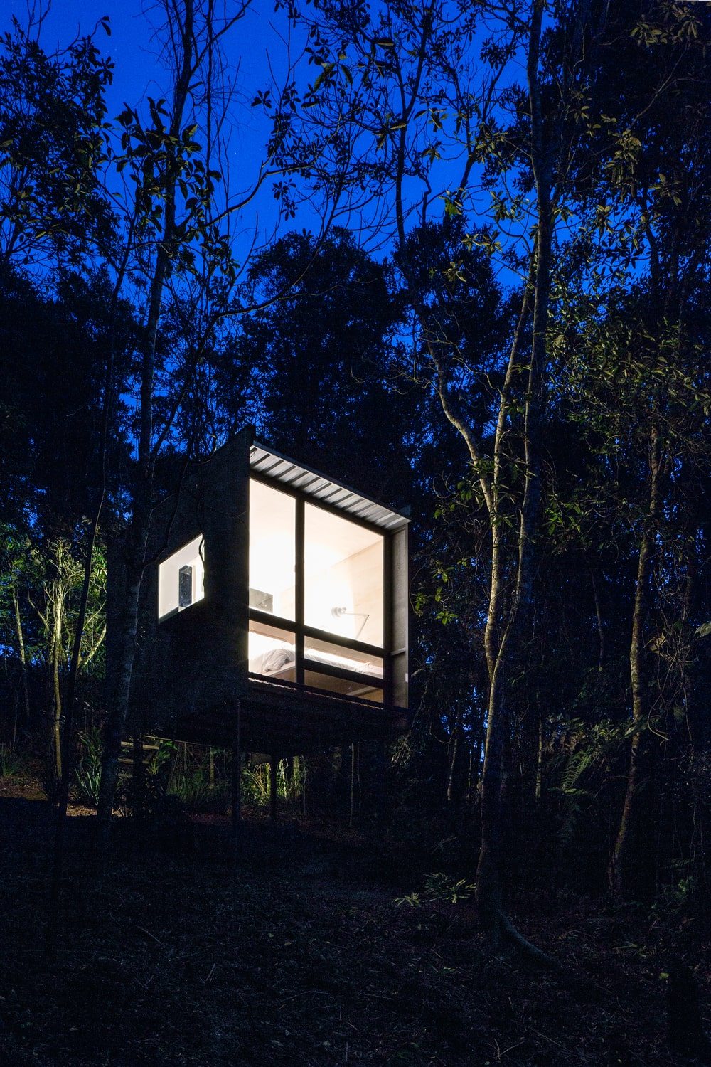 This is a nighttime view of the house showcasing the warm glow of the glass walls making it stand out against the surrounding landscape.
