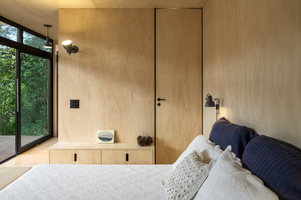 The wooden frame of the bed matches the surrounding wooden walls, floor and ceiling.