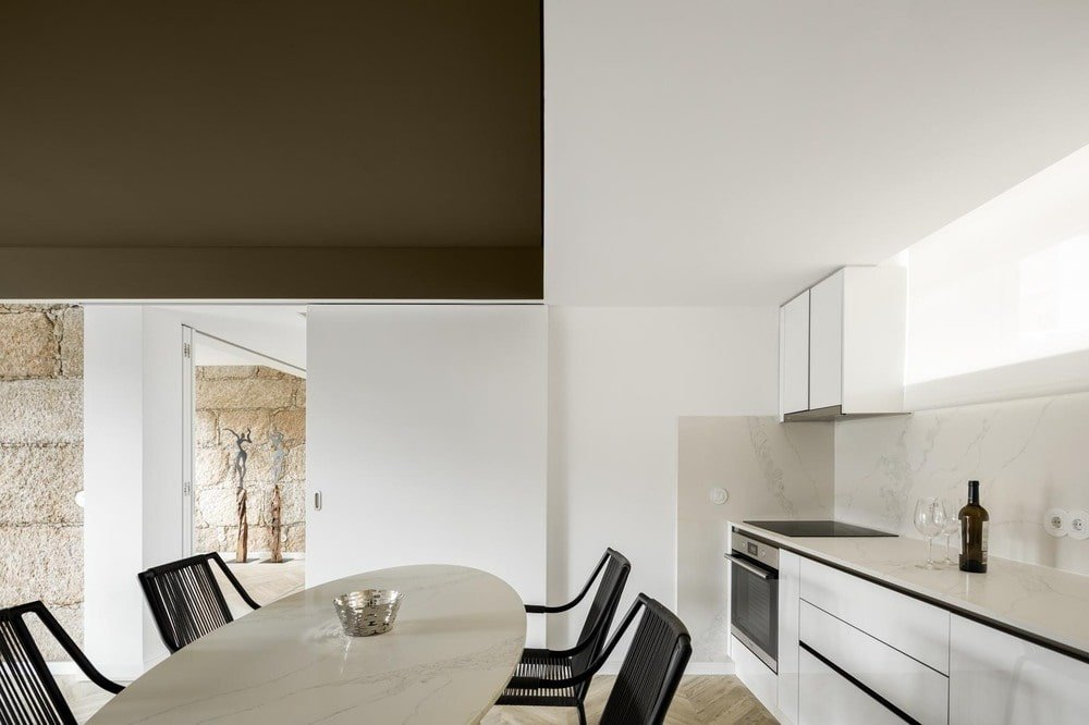 On the side of the dining area is the kitchenette with a cabinetry lining the walls along with a stainless steel oven topped with white counters.