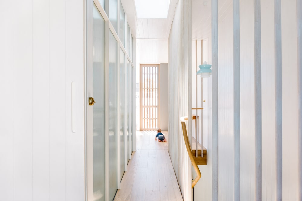 This is a view of one of the house's hallways with glass walls on the sides.