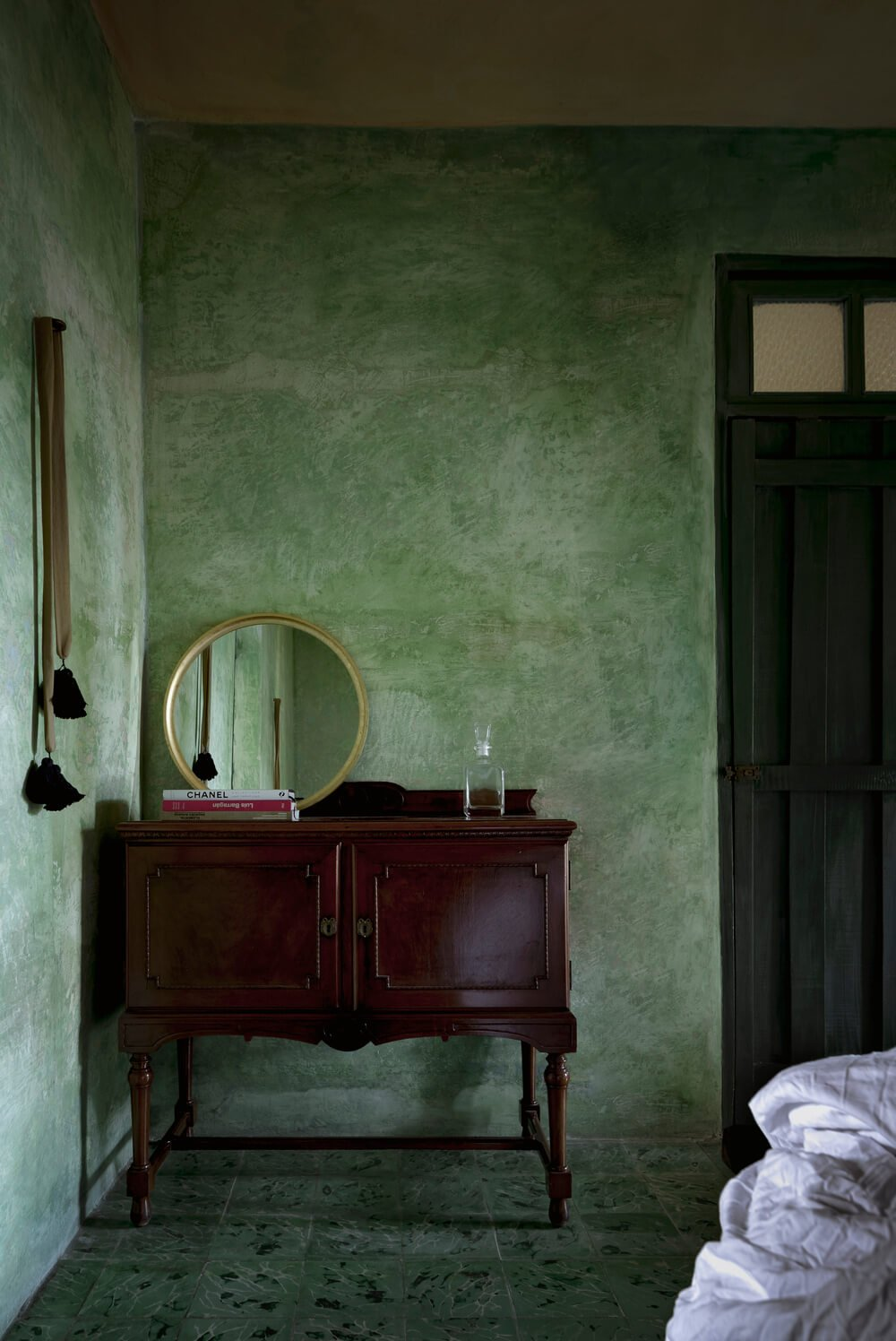 Across from the bed of the bedroom is a dark door with a dark wooden waist-high cabinet fitted with a large round mirror.