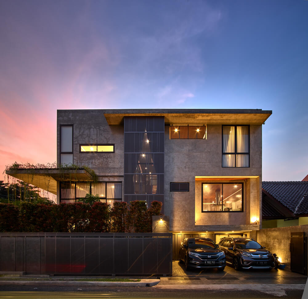 This nighttime view of the front of the house showcases the warm glow of the various windows that pair with the warm outdoor lights of the car port area.