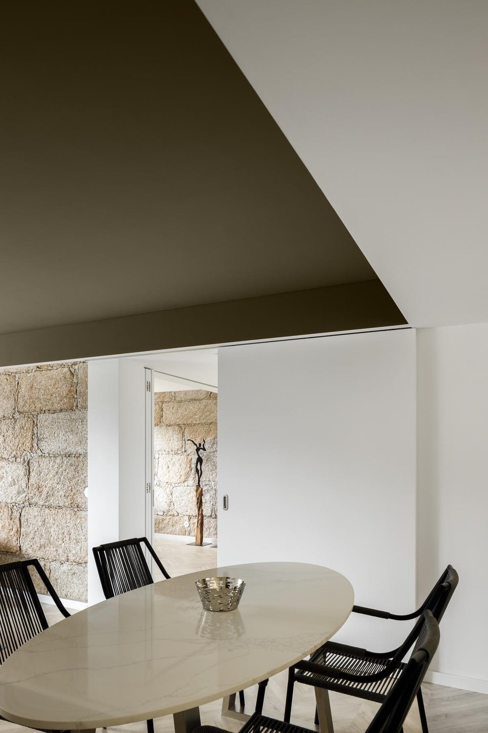 This angle showcases the elliptical shape of the dining table and its beige tone that matches the floor.