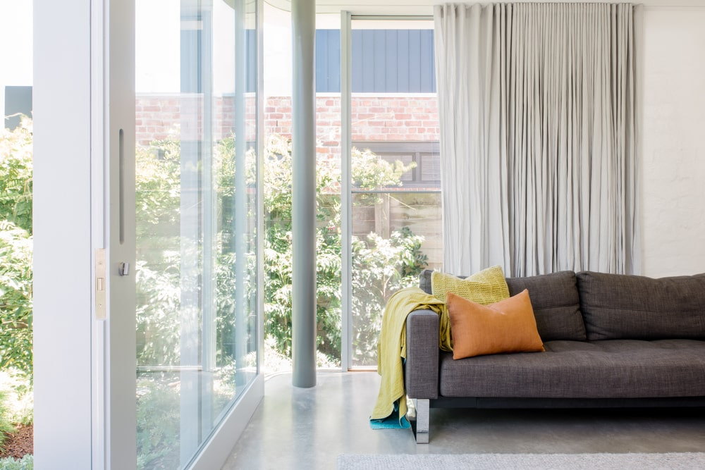 The bright living room has a gray sofa that is brightened by the natural light.