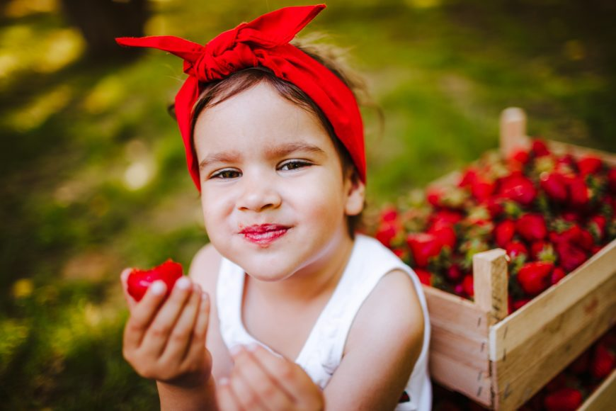 Young Girl in Old School Red Bandana Eating Strawberries