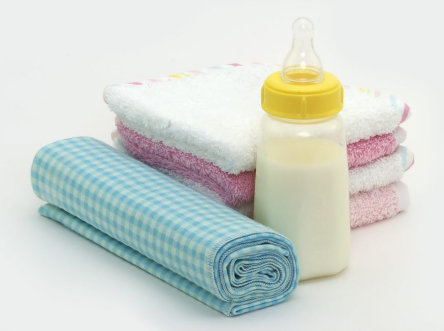 different colors of baby burp cloth with baby bottle on white background