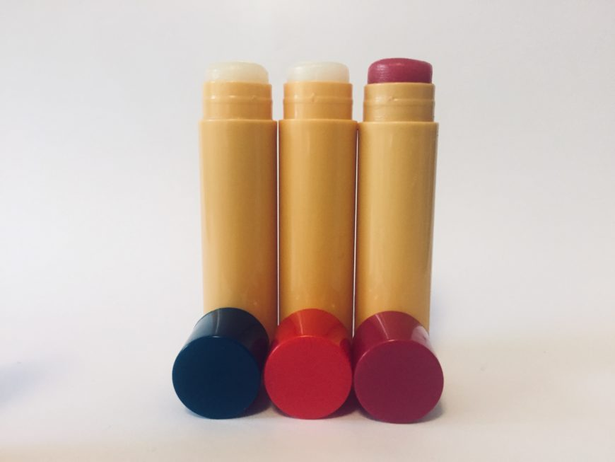 3 Different Colors of Chapstick on White Background