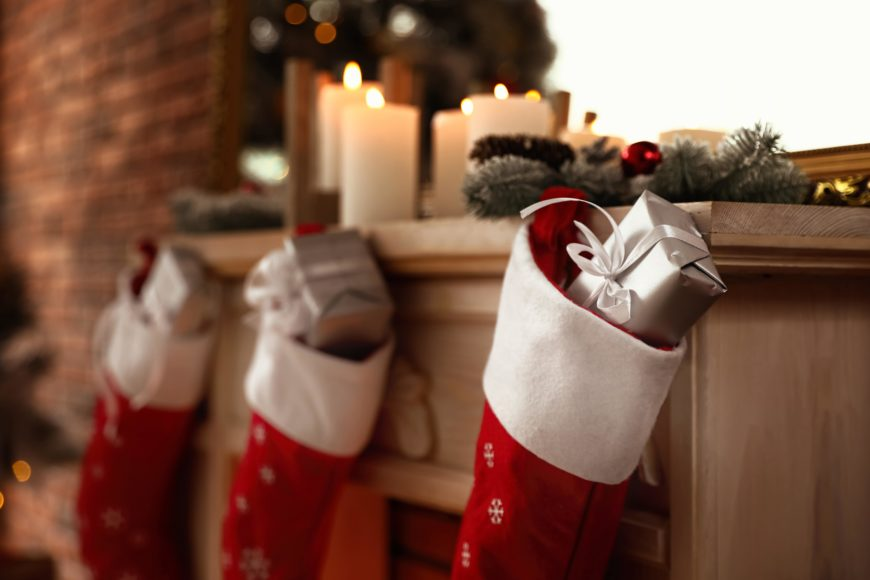 classic christmas stockings stuffed with silver wrapped presents on a decorated mantle