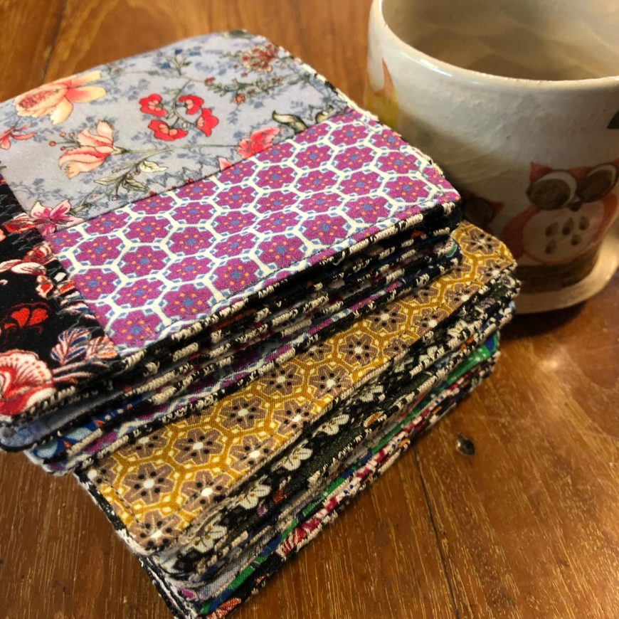 stack of multicolored fabric coasters next to mug on wooden table