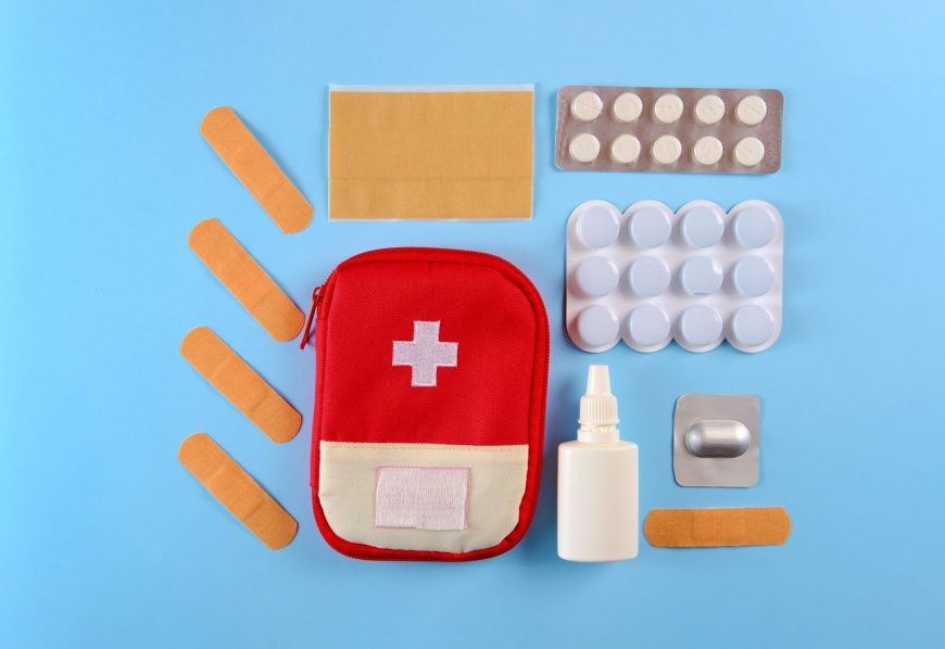 Kitschy First Aid Kit Bandaids Laid out on Blue Background