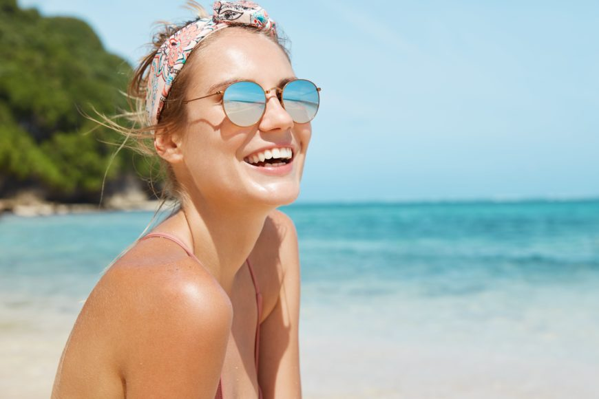 young woman laughing on tropical beach wearing sunglasses and headband