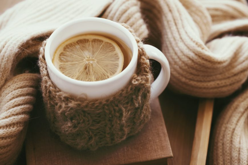 Hot Cup of Lemon Tea in Mug Warmer with Cozy Blanket on Wooden Table
