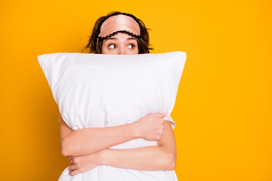 Girl with sleep mask on head holding white pillow infront of orange background