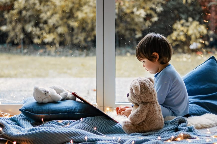 Cute boy reading book in the window sitting on pillow with teddy bear