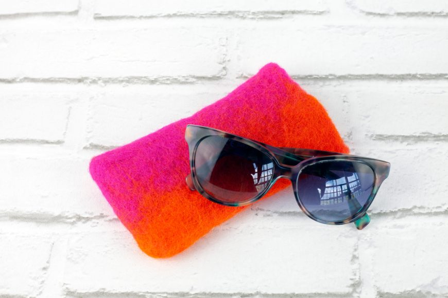 Red Felt Sunglasses Case with Sunglasses on White Brick Background