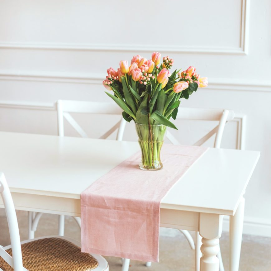 Light pink table runner on white table with bouquet of flowers