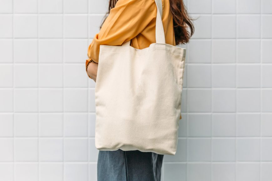 woman holding blank canvas tote bag in front of white tile wall