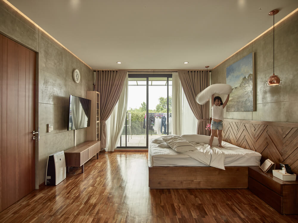The large primary bedroom has a wooden platform bed that matches the hardwood flooring complemented by the walls and natural lighting from the glass doors.