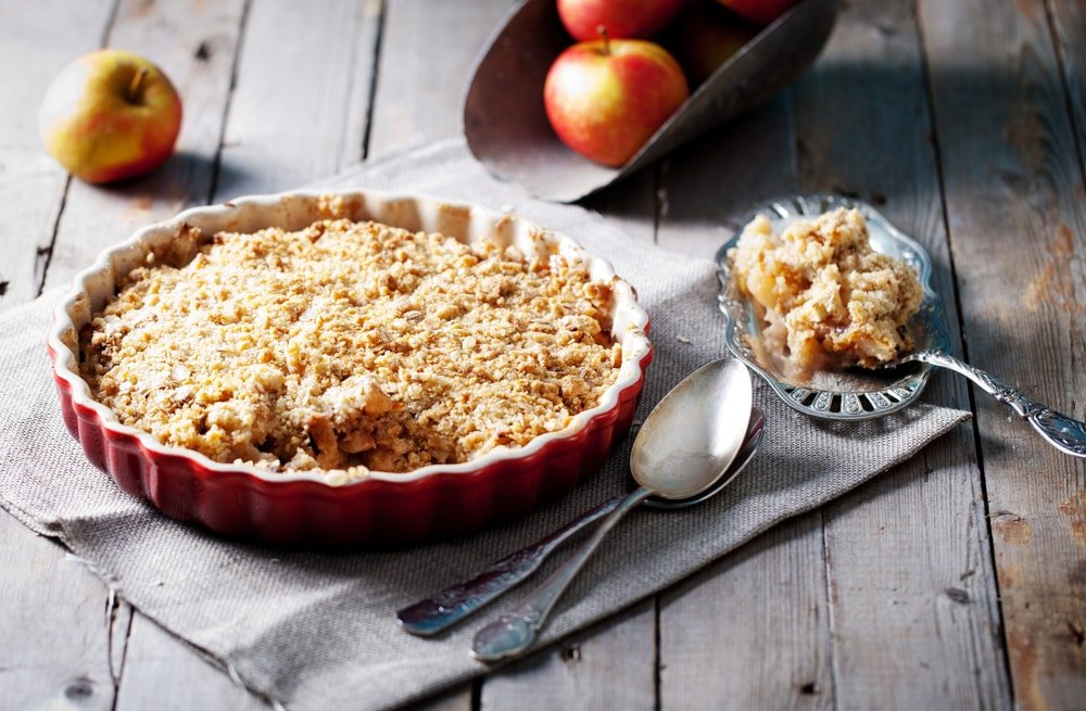 A freshly-baked apple granola crisp on a wooden table.