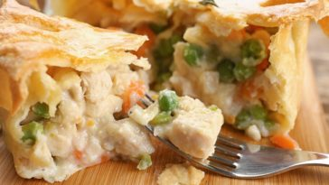 A close look at a chicken pot pie with peas and carrots.
