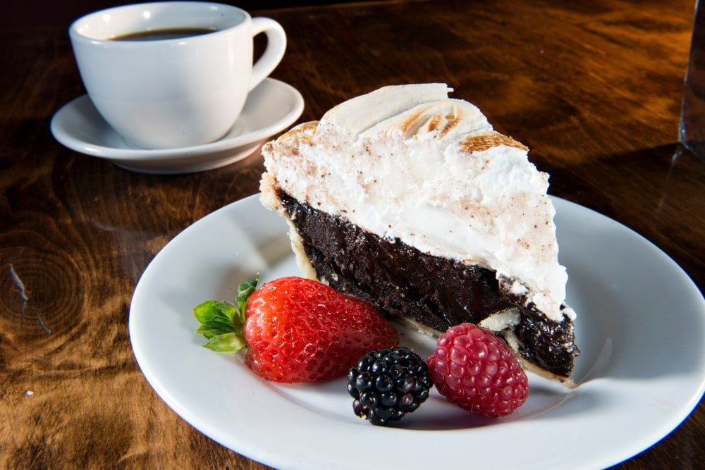 A slice of chocolate meringue pie with berries on the side.