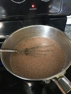 The chocolate pie filling is being mixed in a saucepot.