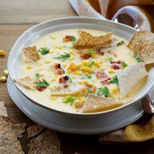 A delicious bowl of corn chowder with crisps.