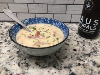 This is a fresh bowl of corn chowder with toppings.
