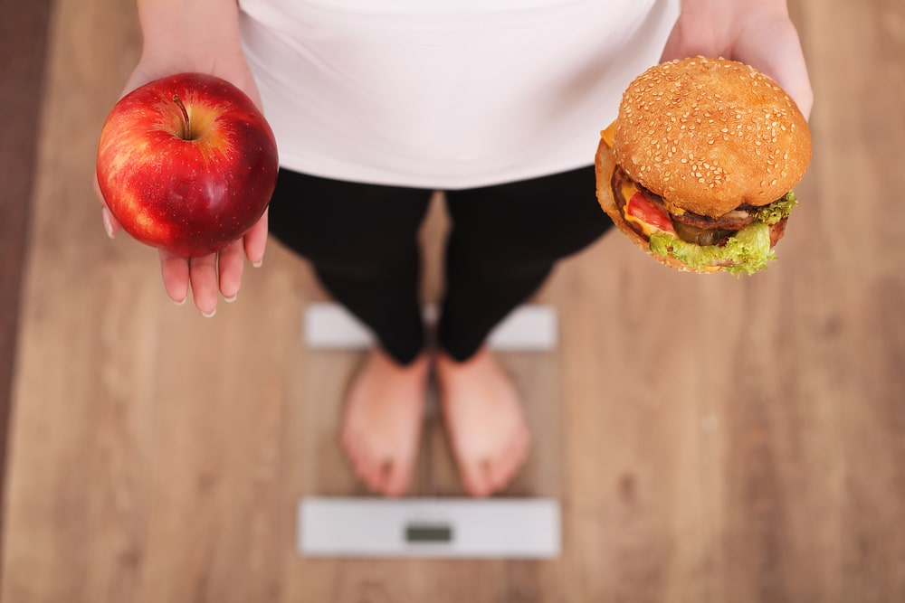 A woman on a weighing scale holding a burger and an apple.