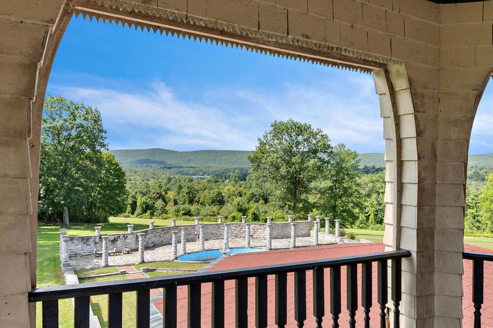This is the balcony of the main house overlooking the swimming pool that can be seen in the distance. Image courtesy of Toptenrealestatedeals.com.
