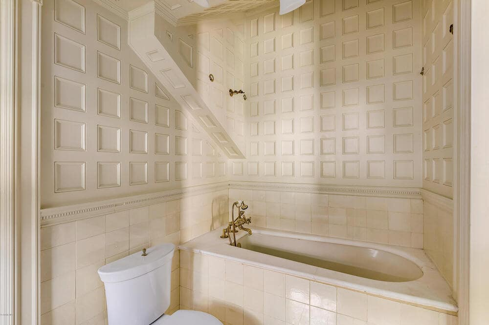 One of the many bathrooms has a consistent beige tone to its walls and ceilings as well as the housing for the bathtub beside the toilet. Image courtesy of Toptenrealestatedeals.com.