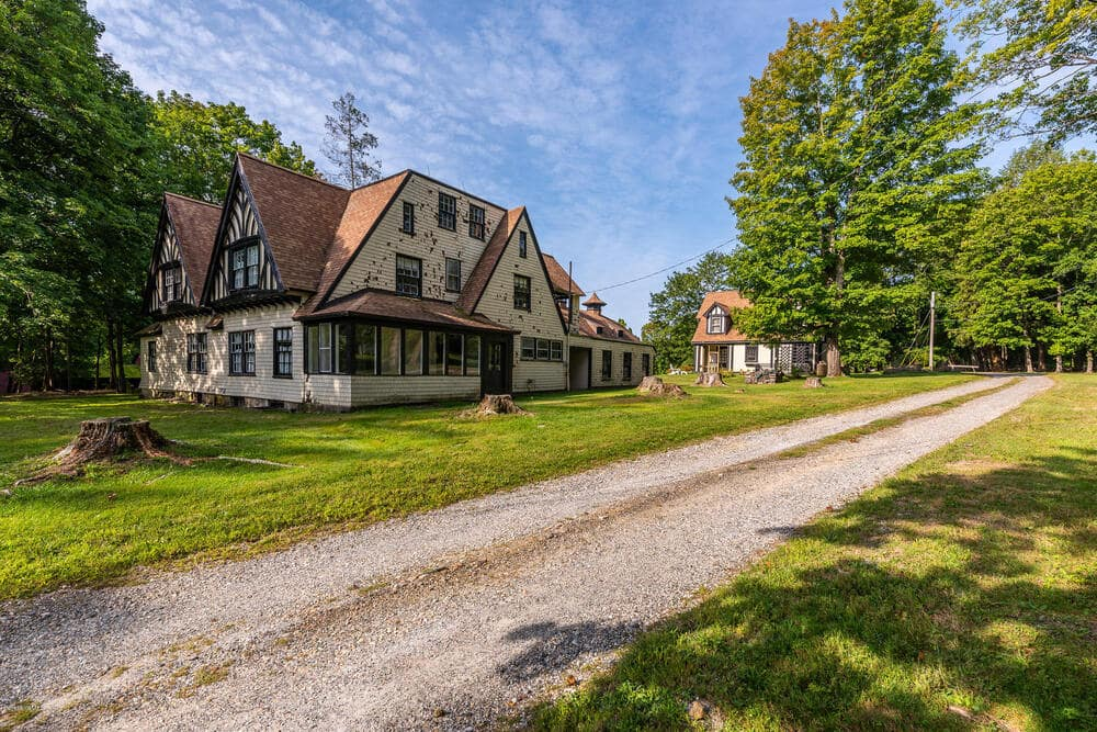 This is the Butler's cottage with two levels, and multiple windows surrounded by large lawns of grass. Image courtesy of Toptenrealestatedeals.com.