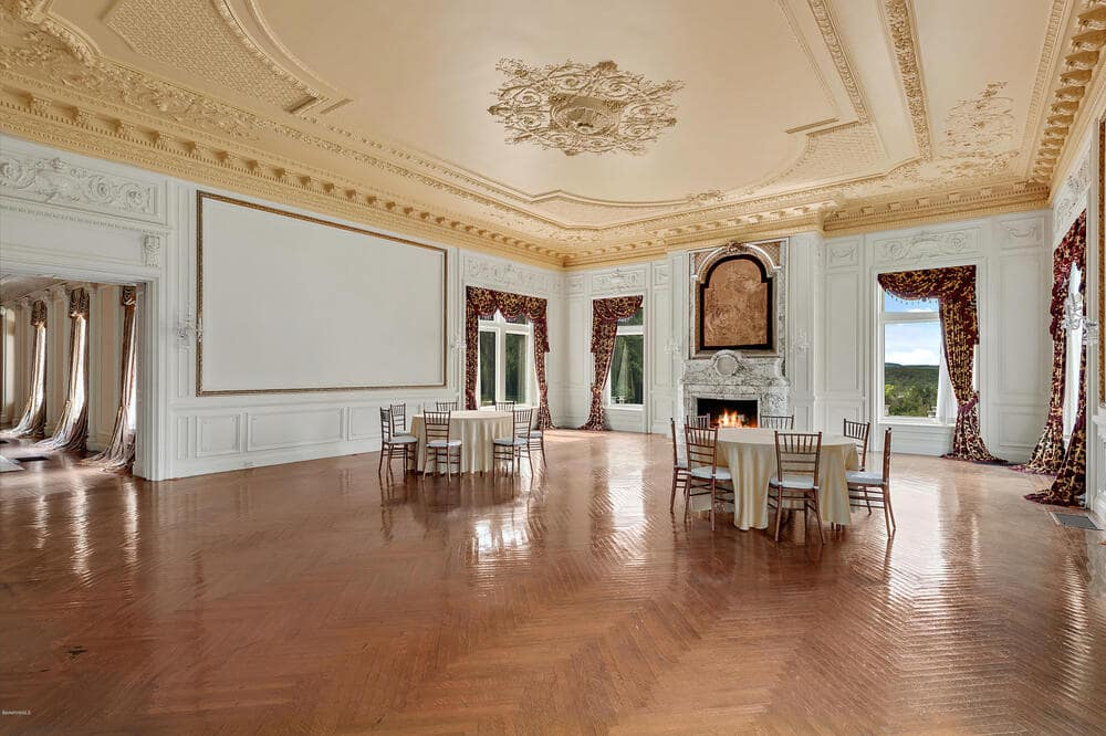 This is the spacious dining room with a tall beige ceiling filled with details over a spacious herringbone hardwood flooring. Image courtesy of Toptenrealestatedeals.com.